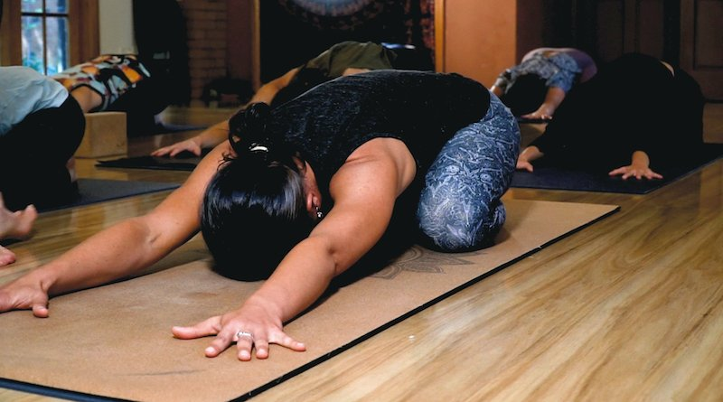 Woman stretches in child pose on sustainable mat, yoga accessory